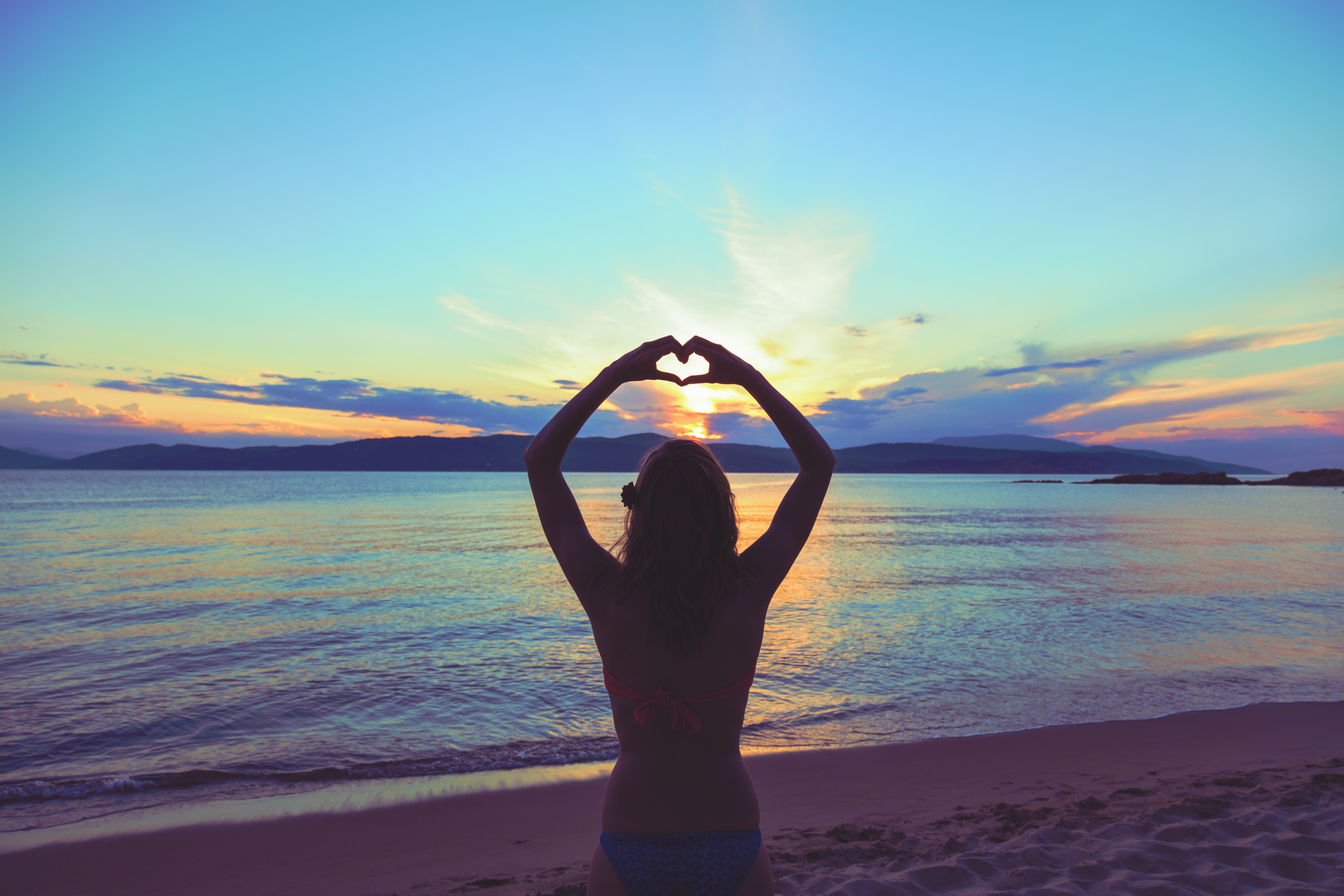 girl,holding,a,heart,shape,for,the,ocean,/,sea.