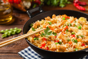 fried,rice,with,chicken.,prepared,and,served,in,a,wok.