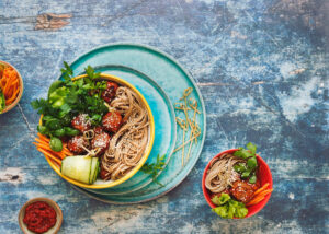 thai,chicken,meatball,noodle,bowls,with,green,vegetables,and,herbs.